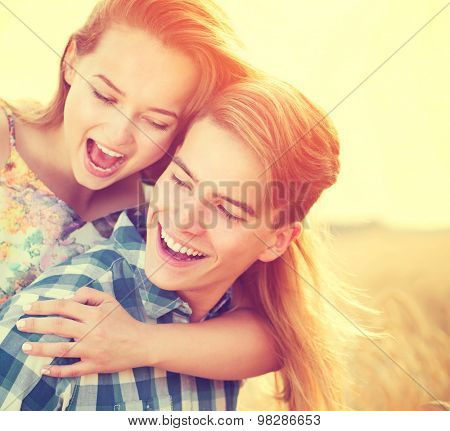 Beauty Couple having fun outdoors, relaxing on wheat field together. Happy girlfriend and boyfriend hugging, love concept. Beautiful Boy and Girl in love together