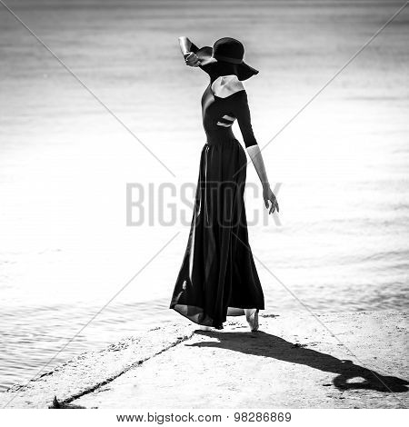 Ballerina In Hat And Long Black Dress Performance. Black And White.