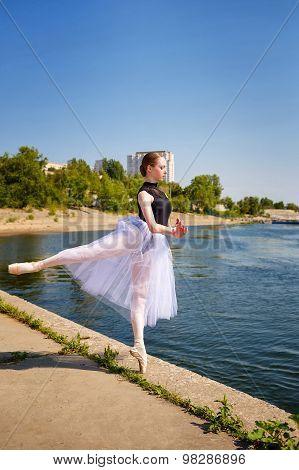 Slim Ballerina In Tutu Dancing On The Riverbank. Arabesque