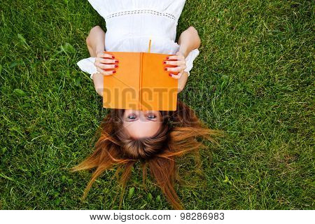 Girl Reading A Book Lying On The Lawn.
