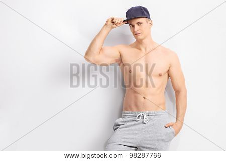 Handsome shirtless man with a dark blue cap looking at the camera and leaning against a gray wall