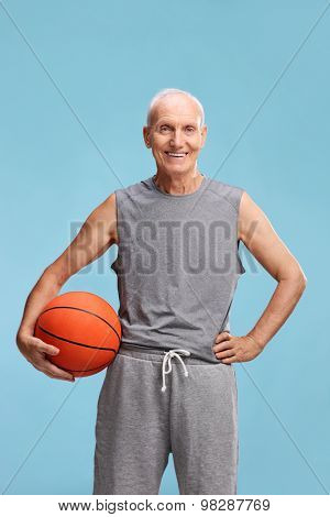 Vertical studio shot of a senior man in sportswear holding a basketball and looking at the camera on blue background