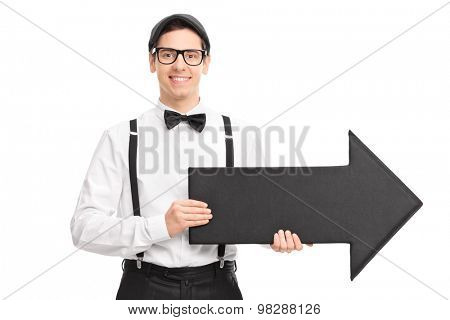 Elegant young man with black bow-tie and suspenders holding a big black arrow pointing right isolated on white background