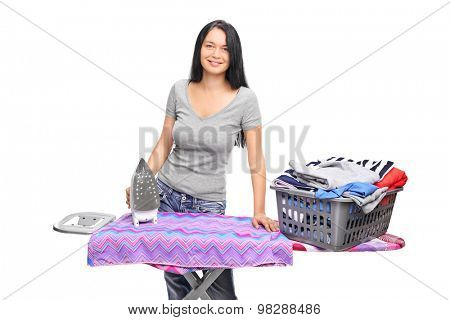 Cheerful woman posing behind an ironing board with a laundry basket full of clothes on it isolated on white background