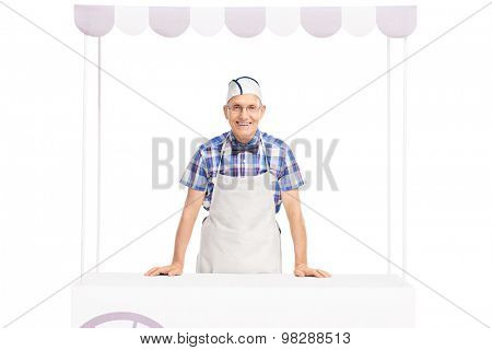 Senior ice cream seller with a white cap and apron standing behind an ice cream stand and looking at the camera isolated on white background