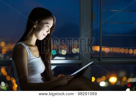 Woman using the tablet pc at night