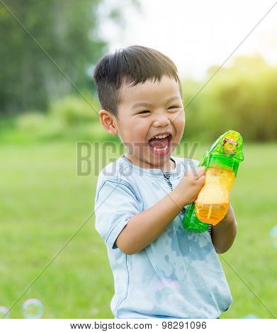 Thrilled boy play bubble blower at park