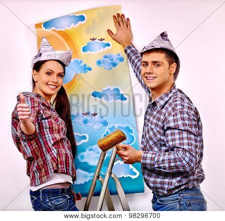 Happy family glues wallpaper at home. Renovation of apartments