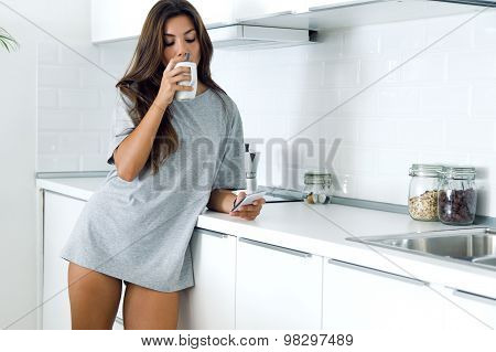 Beautiful Young Woman Drinking Coffee And Using Her Mobile Phone At Home.