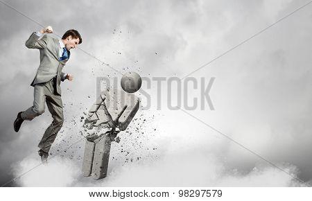 Furious businessman crashing with strike stone man figure