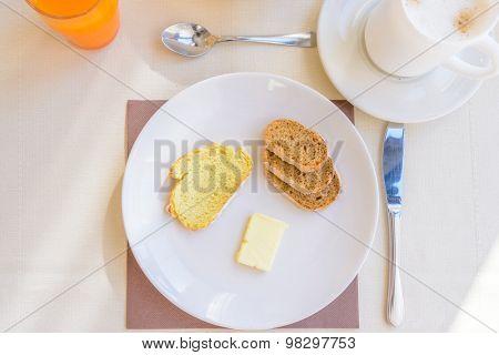 Breakfast including coffee, orange juce, bread, and butter.