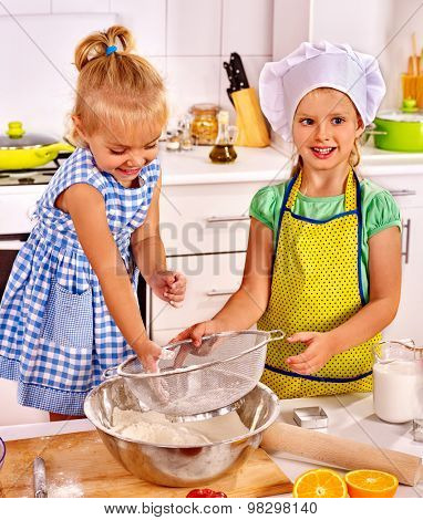 Child with rolling-pin dough at kitchen. Kids cooking at home