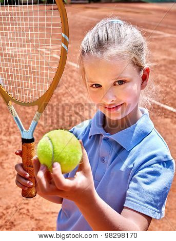 Sport kids girl with racket and ball on  brown  court. Child tennis player.
