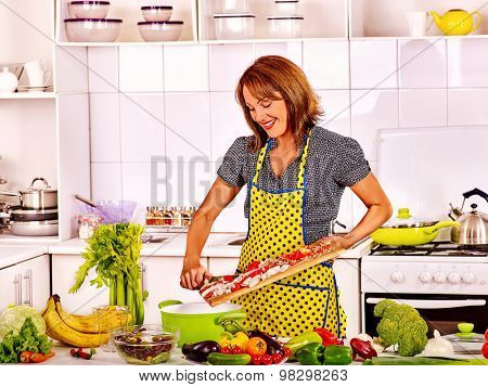 Female preparing food at kitchen. Woman cooking at home