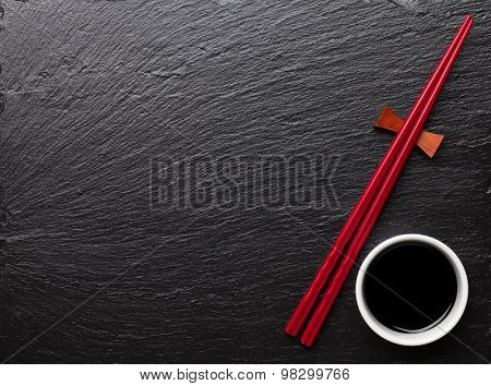 Japanese sushi chopsticks and soy sauce bowl on black stone background. Top view with copy space
