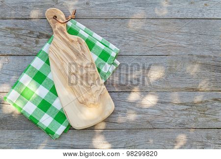 Empty wooden garden table with cutting board over tablecloth. Top view with copy space