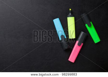 Colorful highlighters on leather desk table. Top view with copy space
