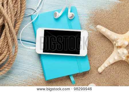 Smartphone and notepad on sea sand with starfish. Top view with copy space