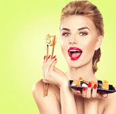 Постер, плакат: Beauty Woman eating Sushi Beauty Fashion model girl eating Sushi rolls Chopsticks Beautiful sexy