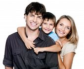 stock photo of family bonding  - Happy young family with pretty child posing on white background - JPG