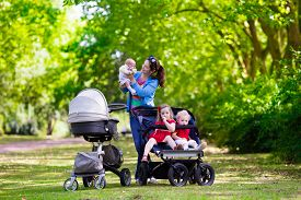 stock photo of twin baby  - Young mother walking in a park with children in pushchair - JPG