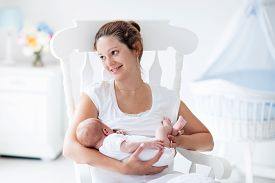 image of nursing  - Young mother holding her newborn child - JPG