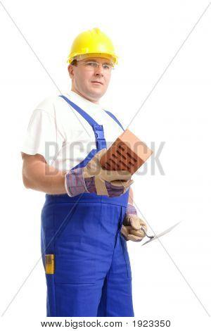 Construtor com o tijolo e a colher de pedreiro