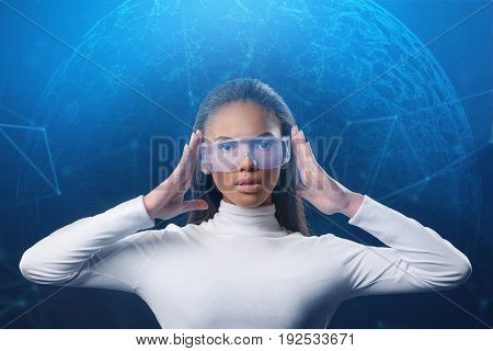 All world internet connection on the touch screen. Pensive young businesswoman is touching her eyewear and looking forward with interest. Future concept