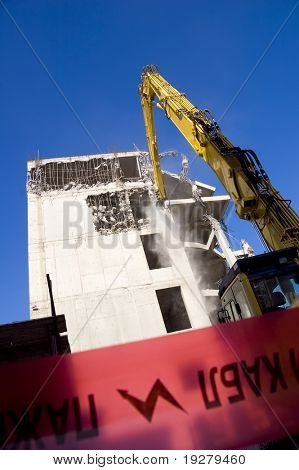 Destruction of concrete wall of old building with excavators