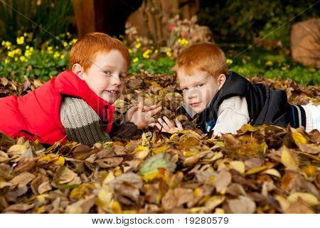 Two happy and smiling brothers lying in a pile of autumn leaves in the garden
