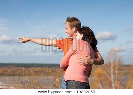 Young man shows to his pregnant wife their future home location