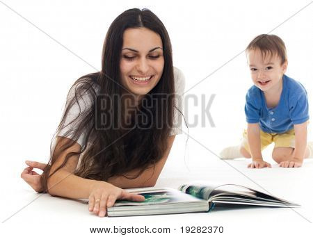Young mother reading book on floor with her son