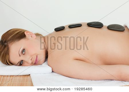 Blond-haired woman relaxing with pebbles on her back