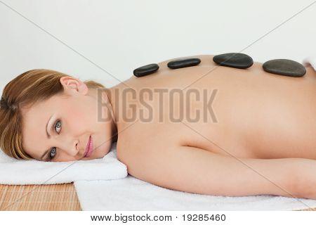 Stülpnase Woman relaxing mit Kieselsteinen auf dem Rücken