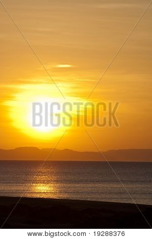Orange and vibrant red sunset with sun behind mountainous horizon and ocean