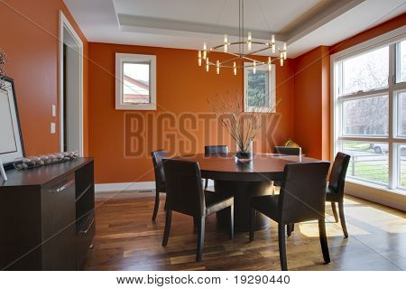 Luxury Dining Room with Orange Walls. Brightly lit with large windows.