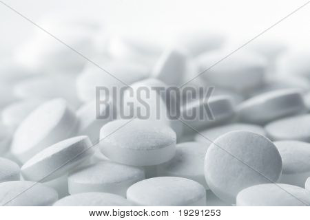 High key shot of white pills brightly lit.