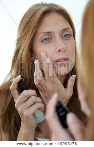 Mulher bonita, colocando a base no rosto