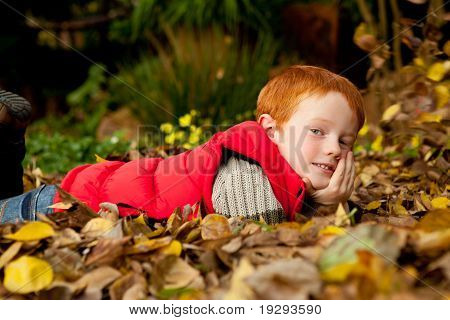 A happy young red haired boy is lying in a pile of colorful autumn / fall leaves in a garden or park