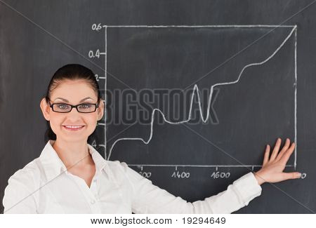 Scientist showing charts while standing near the blackboard