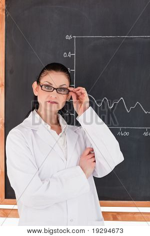 Female scientist standing near the blackboard