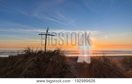 Cross and Jesus on a sand dune on a beach as the sunsets.