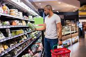 Young african man buying vegetables in grocery section at supermarket. Black man choose vegetables i poster