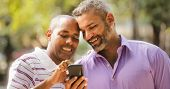 Happy Lgbt Gay Couple Looking At Pictures On Mobile Phone poster