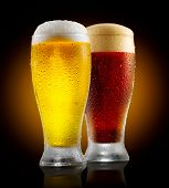 Beer. Cold Craft light and dark Beer in a glass with water drops. Two Craft Beers close up isolated  poster