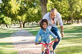 Lovely father teaching son riding bike at park. Happy father helping excited son to ride a bicycle a poster