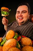 Fat man eating fast food hamberger. Breakfast on fork for overweight person. Junk meal leads to obes poster