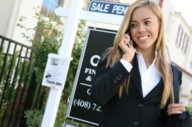 stock photo of real-estate agent  - A beautiful young real estate agent woman on the phone - JPG