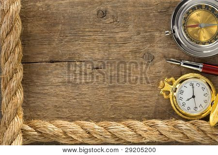 ship ropes and compass with pen on old vintage wooden background