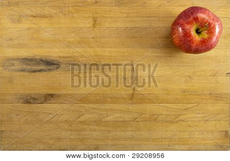 Red Apple On Worn Cutting Board